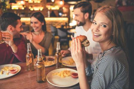 Gelukkige vrienden het eten van hamburgers, praten en lachen tijdens samen tijd doorbrengen in cafe Stockfoto