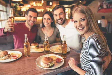 幸せな友人のカメラを見て、カフェで一緒に時間を過ごしながら笑みを浮かべて 写真素材