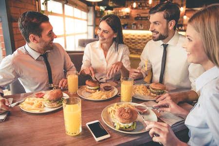 사업 사람들은 카페에서 점심을 먹고 이야기하고 웃고 있습니다. 스톡 콘텐츠