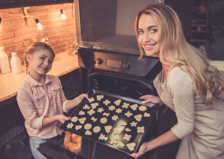 Cute little girl and her beautiful mom are putting cookies into the oven and smiling while baking in kitchen at home Stock Photo
