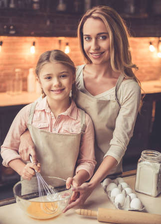 Cute little girl and her beautiful mom in aprons are whisking eggs and smiling while baking in kitchen at home