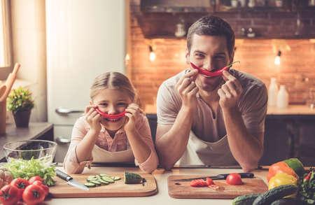 귀여운 소녀와 그녀의 잘 생긴 아빠는 고추를 들고 집에서 부엌에서 요리하는 동안 웃 고있다.