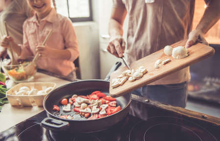 Cropped image of cute little girl and her beautiful parents cooking together in kitchen at home