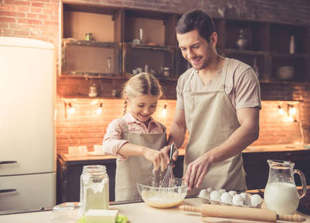 Cute little girl and her handsome dad in aprons are whisking eggs and smiling while baking in kitchen at home Stock Photo