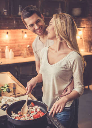 Beautiful young couple is smiling while cooking together in kitchen at home Zdjęcie Seryjne