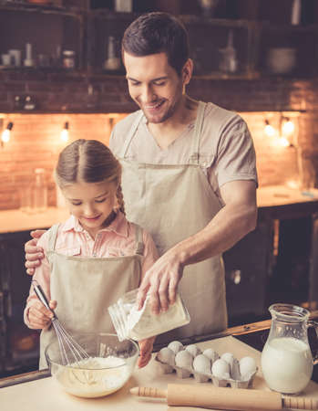 Cute little girl and her handsome dad in aprons are whisking eggs with flour and smiling while baking in kitchen at home