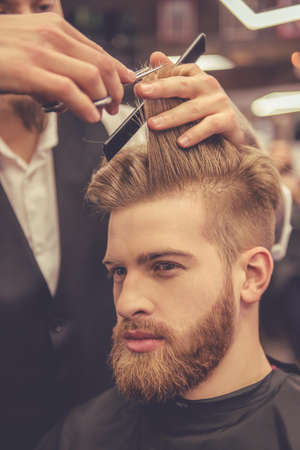 Handsome bearded man is looking forward while getting haircut by hairdresser at the barbershop