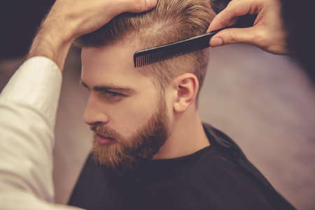 De knappe gebaarde mens verheugt zich terwijl het hebben van zijn haar door kapper bij de herenkapper wordt gesneden