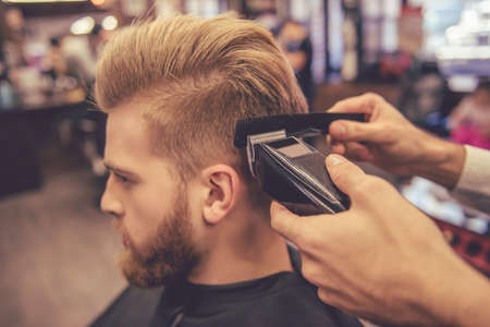 clippers comb: Side view of handsome bearded man getting haircut by hairdresser at the barbershop