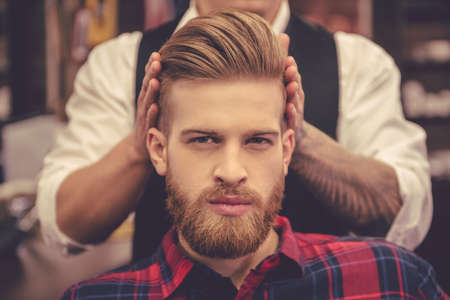 Handsome bearded man is looking at camera while getting haircut by hairdresser at the barbershop Zdjęcie Seryjne