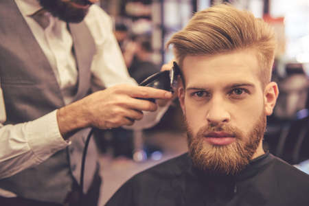 clippers comb: Handsome bearded man is looking forward while getting haircut by hairdresser at the barbershop