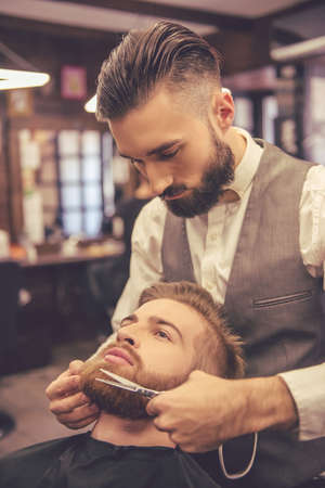 Handsome bearded man is having his beard cut by hairdresser at the barbershop