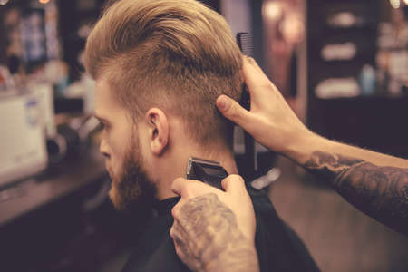 clippers comb: Back view of handsome bearded man getting haircut by hairdresser at the barbershop