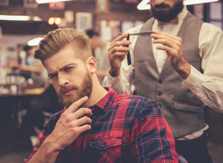 Handsome man is touching his beard while sitting in chair at the barbershop, in the background barber is holding a straight razor Stock Photo