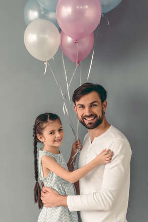 Cute little girl and her handsome father are holding balloons, looking at camera and smiling, on gray background