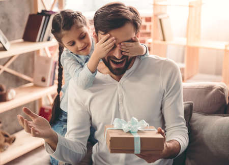 Cute little girl is giving her handsome father a gift box. Both are sitting on couch at home and smiling Stock Photo