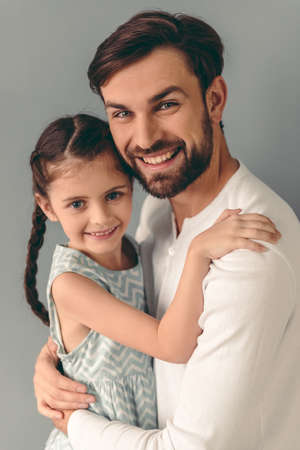 Portrait of cute little girl and her handsome father looking at camera and smiling, on gray background