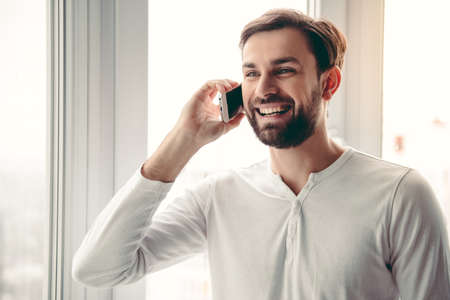 Handsome young man is talking on the mobile phone and smiling while standing near the window