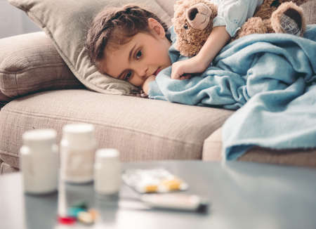 sadly: Sick little girl covered in blanket is hugging teddy bear and looking sadly on medicine while lying on couch