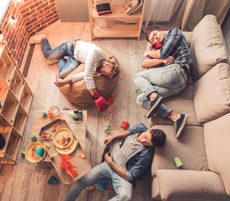 mess: Top view of guys sleeping in messy room after having a party at home