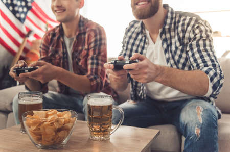 Des mecs séduisants jouent à des jeux vidéo, boivent de la bière et sourient assis sur un canapé à la maison