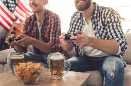 Des mecs séduisants jouent à des jeux vidéo, boivent de la bière et sourient assis sur un canapé à la maison Banque d'images - 70052518