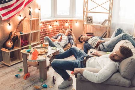 messy room: Guys are sleeping in messy room with bottles of beer in their hands after having a party at home