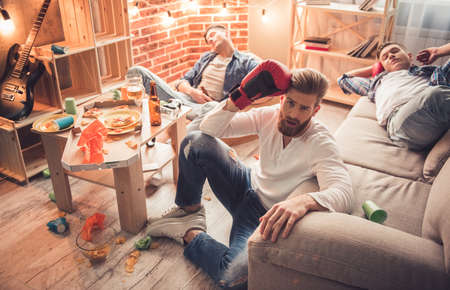 messy room: Guys are sleeping in messy room after having a party at home Stock Photo