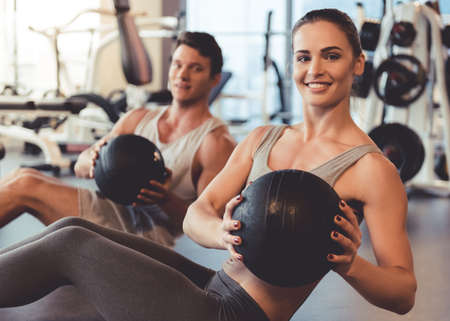 Attractive young muscular man and woman are working out with balls in gym