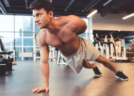 laying abs exercise: Attractive young muscular man is doing pushups while working out in gym