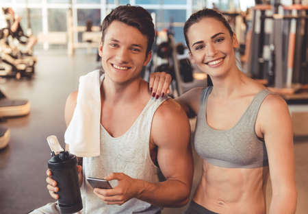 Attractive young sports people are talking and smiling while standing in gym