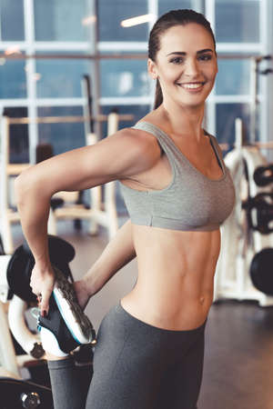 elasticidad: Attractive young woman is looking at camera and smiling while stretching body in gym Foto de archivo