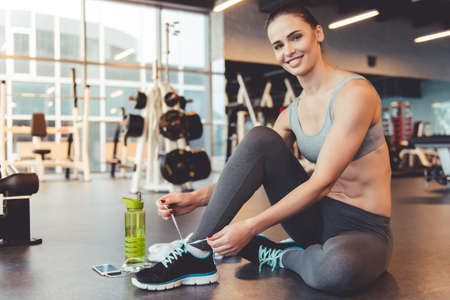 Attractive young woman is lacing up her training shoes, looking at camera and smiling while working out in gym Stock Photo