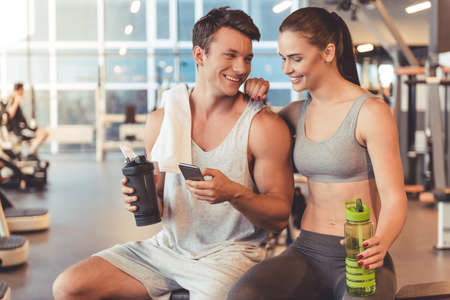 Attractive young sports people are holding bottle of water, talking and smiling while resting in gym