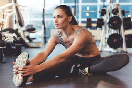Attractive young woman is smiling while stretching body in gym