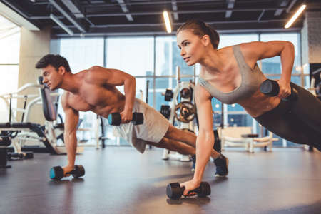 Attractive young sports people are working out with dumbbells in gym