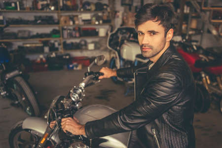 clothing shop: Attractive guy in leather jacket is looking at camera while sitting on the motorcycle in the repair shop