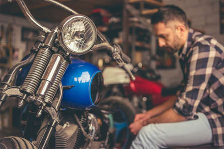 Handsome man is repairing a motorcycle in the repair shop Stock Photo