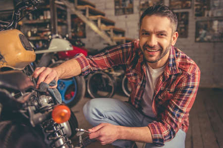 Handsome man is looking at camera and smiling while repairing a motorcycle in the repair shop