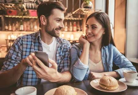 Happy young couple is using a smartphone, looking at each other and smiling while sitting at the cafe