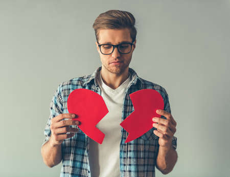 sadly: Handsome romantic guy is holding a broken heart and looking sadly at it, on gray background