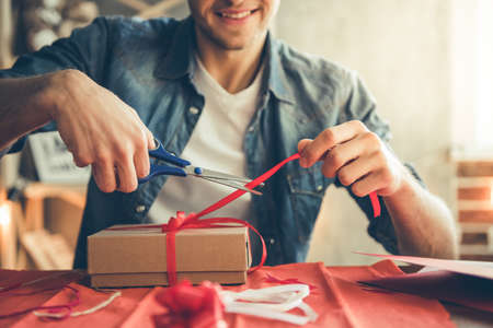 Handsome romantic guy is smiling while making present for his better half