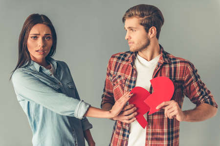 two and a half: Handsome guy is holding two halves of paper heart, girl is refusing to take a half, on gray background