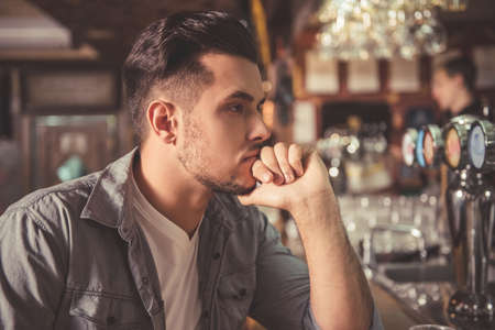 Handsome pensive guy is looking forward and thinking while leaning on the bar counter in pub