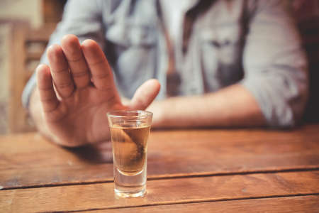 Cropped image of man showing stop gesture and refusing to drink