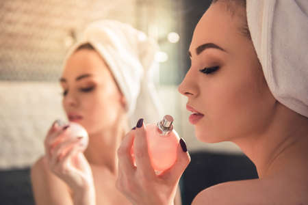 Beautiful girl in bath towel is using perfume while looking into the mirror in bathroom