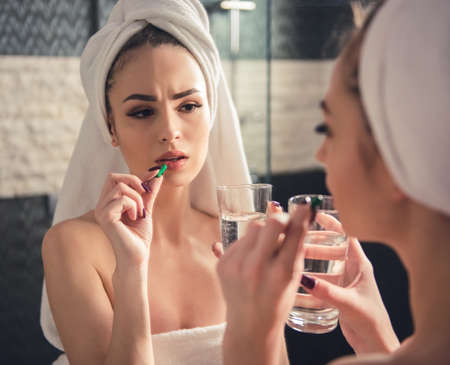 Beautiful girl in bath towel is taking a pill with water while looking into the mirror in bathroom Stock Photo