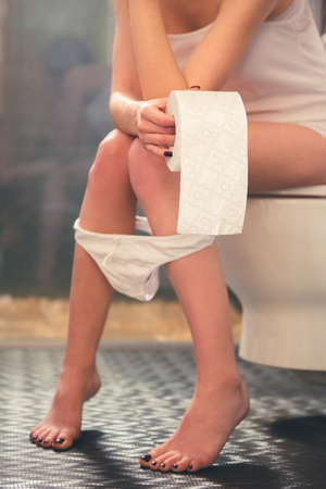 a toilet stool: Cropped image of beautiful girl holding a toilet paper while sitting on toilet