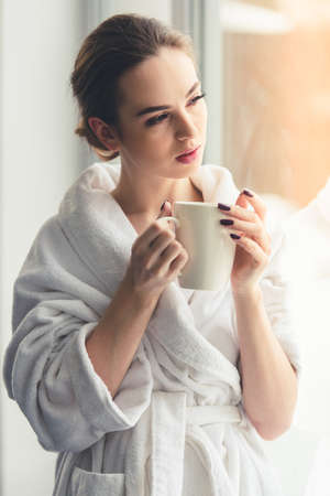 bath robe: Beautiful girl in bath robe is holding a cup and looking out the window Stock Photo