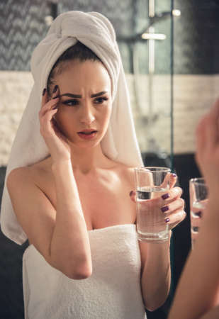 Beautiful girl in bath towel is feeling pain, holding a glass of water and looking into the mirror in bathroom Stock Photo
